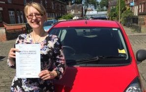Helen showing off her pass certificate with car awaiting to be driven away